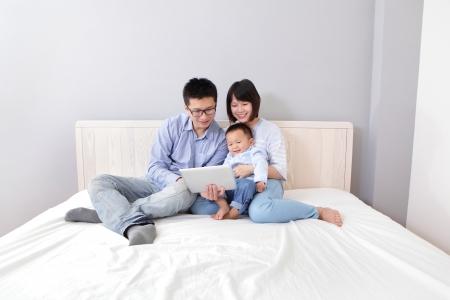 familia abrazo: familia feliz de madre, padre, hijo sentado en la cama en su casa que se divierten usando un Tablet PC, gente asi�tica