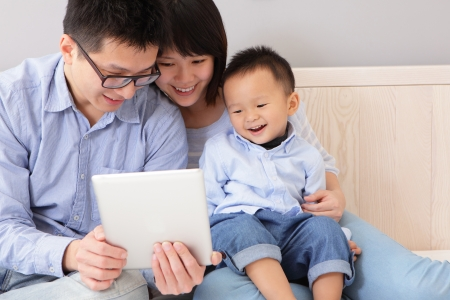 young asian girl: closeup of a happy, family of mother, father, son sitting on bed at home having fun using a tablet pc, asian people