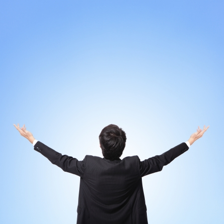 back up: back view of business man arms up and looking to empty copy space isolated on blue sky background, asian model