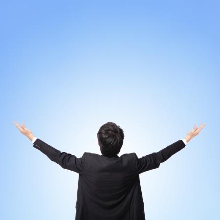 Vue arrière du bras homme d'affaires à la recherche et à l'espace de copie vide isolé sur fond de ciel bleu, modèle asiatique