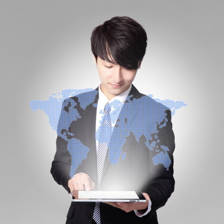 world in your hand - handsome business man using touch screen tablet pc, concept for business and cloud computing, asian man model photo