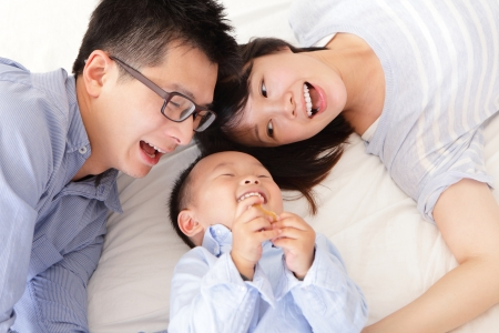 Happy family with children in bed, asian people photo