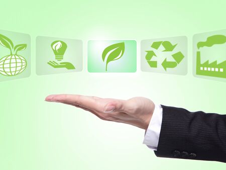 kinds: green eco icons concept , business man hand palm holding all kinds of icon about eco with green background Stock Photo