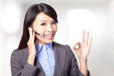 beautiful  customer  service  operator  woman with headset and smiling ,one hand touching the headset and the other hand show to ok sign, asian woman  photo