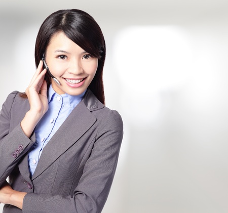 beautiful  customer  service  operator  woman with headset and smiling ,one hand touching the headset ,asian woman  photo