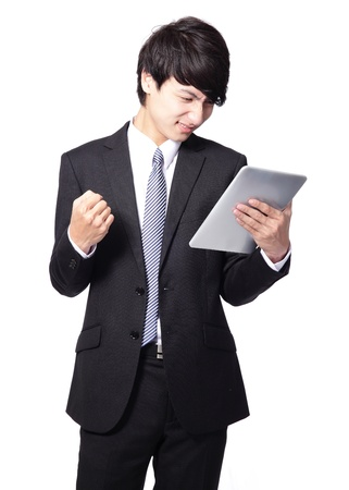 asian businessman using touch pad with annoyed face, one hand made a fist photo