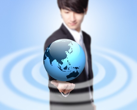 hand holding globe: Young businessman holding a globe with asia map isolated on blue background, asian model