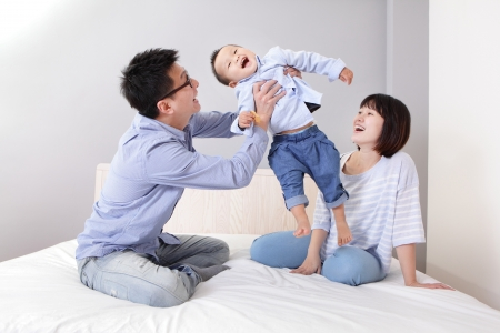 happy father hug his son with smile mother sitting on bed at home, asian family photo