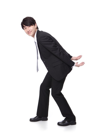 work load: portrait of a happy business man holding something heavy on his back in full length isolated on white background, asian model Stock Photo