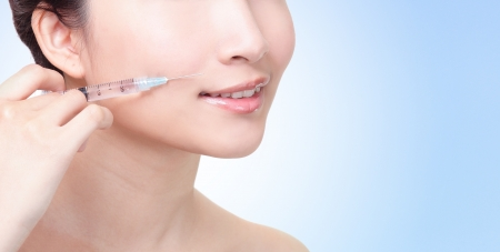 face lift: Cosmetic injection in the female face. Lips zone. Isolated on blue background, asian beauty woman