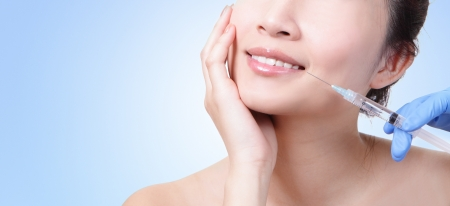 botox: Cosmetic injection in the female face. Lips zone. Isolated on blue background, asian beauty woman