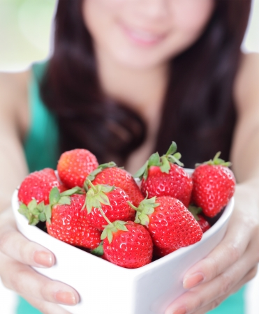 Strawberry - close up of beautiful woman showing fresh strawberries, asian beauty mode photo