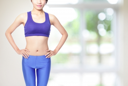pretty sporty woman with nice body isolated on green background, asian model photo