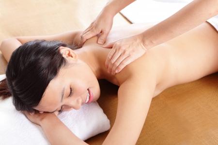 massaggio collo: Primo piano della donna nel salone di bellezza con massaggio di spalla, modello di donna asiatica