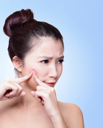 unhappy Woman finding an acne on her face isolated on blue background, asian beauty photo