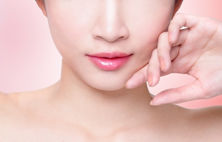 Female lips closeup. Beautiful smile of young fresh woman.  Isolated over pink background. asian model photo