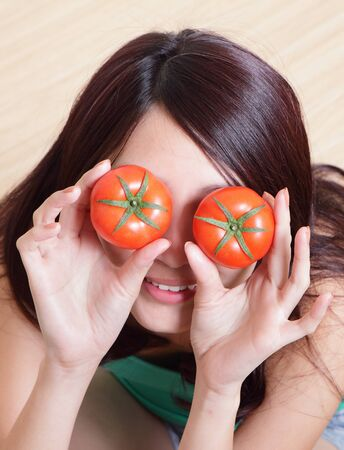 funny girl showing tomato with smile face, cover her eyes, high angle view , asian woman model photo