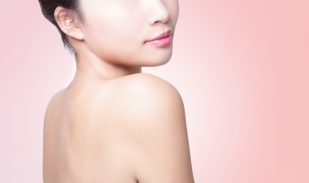 naked female body: Rear view of a young woman shoulder isolated on pink background, asian beauty Stock Photo