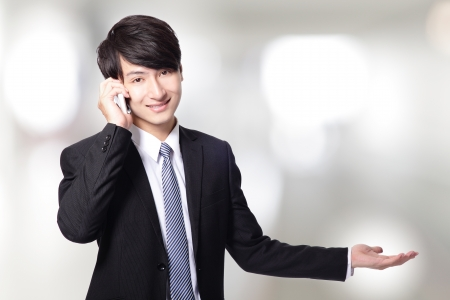 businessman showing copy space with phone isolated on gray background, copy space, asian model photo