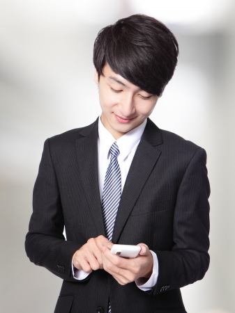 businessman touching smart phone isolated on gray background, asian model photo