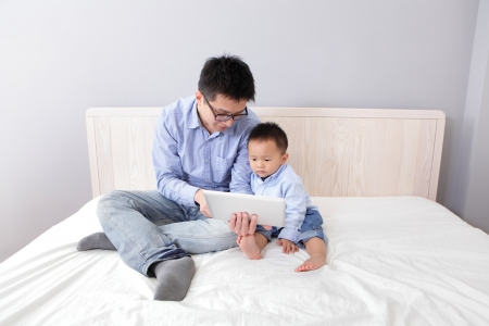 Father and son smile and happy using tablet pc on bed at home, asian people photo