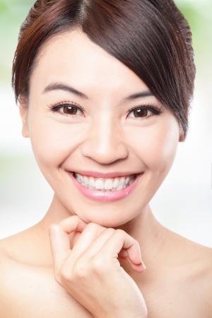 Smile happy Face of beautiful woman with health teeth and skin care isolated over green background. Beautiful young asian woman model photo
