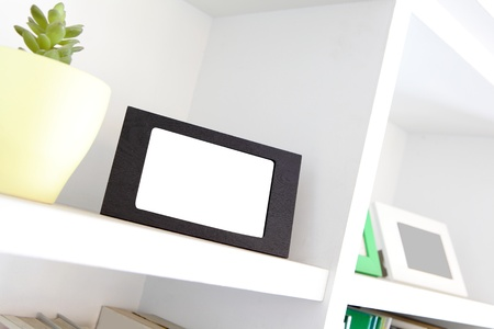 blank photo frame with copy space on white bookshelf at home Stock Photo - 19015684