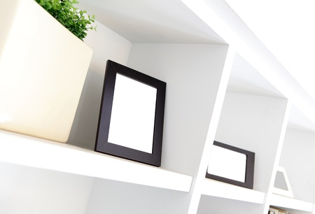 blank photo frame with copy space on white bookshelf at home Stock Photo - 19015589