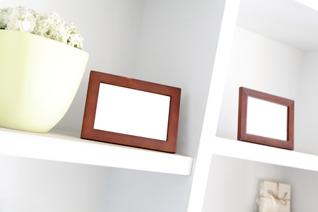 blank photo frame with copy space on white bookshelf at home photo