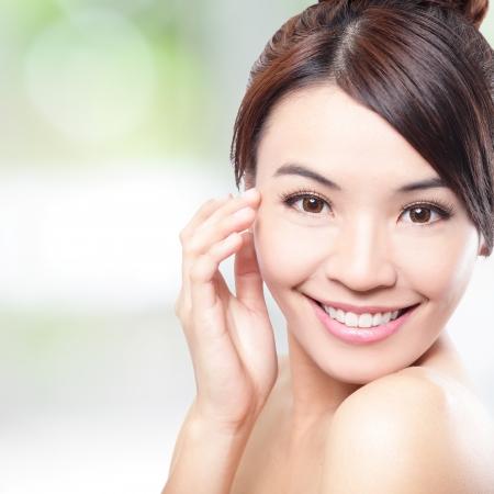 sonrisa: Mujer hermosa cara de la sonrisa con la cara limpia la piel y el tacto dedo con los ojos, concepto para el cuidado de los ojos y la piel, sobre la naturaleza de fondo verde, la belleza asi�tica