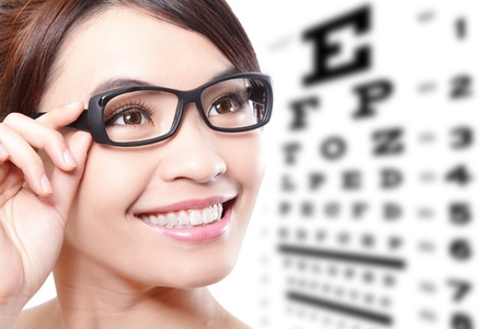 eye test: beautiful woman with glasses on the background of eye test chart, eye care concept, asian beauty