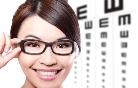 oculista: hermosa mujer con gafas en el fondo de la tabla optométrica prueba, el concepto de cuidado de los ojos, la belleza asiática Foto de archivo
