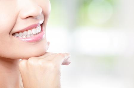 Mooie jonge vrouw tanden dichtbij met kopie ruimte aan de rechterkant. Geïsoleerd op groene achtergrond, Aziatische schoonheid model Stockfoto