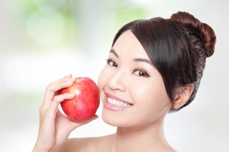 over eating: Beautiful young woman eating red apple with health teeth. Isolated over green background, asian beauty model