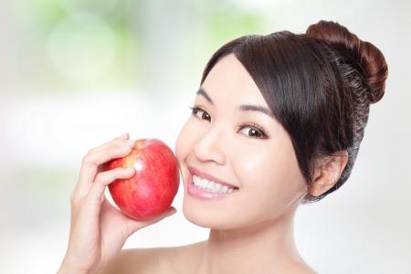 dentista: Mujer joven hermosa que come la manzana roja con los dientes de la salud. M�s de fondo, el modelo de belleza asi�tica verde