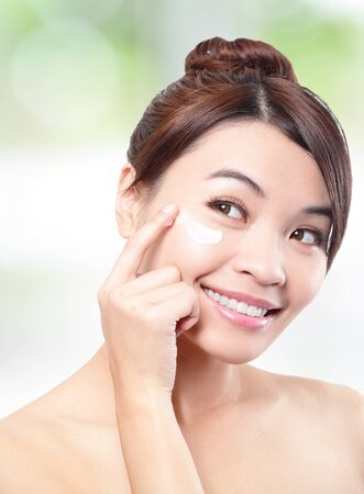 eye cream: Beauty young woman applying cosmetic cream under eyes, concept for eye and skin care,  asian beauty
