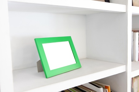blank photo frame with copy space on white bookshelf at home Stock Photo - 19436798