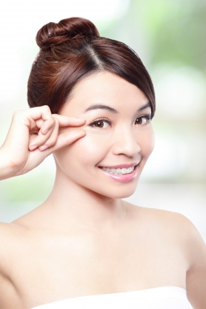 Beautiful woman smile face and finger touch her eyes with clean face skin, concept for eye and skin care, over nature green background, asian beauty photo
