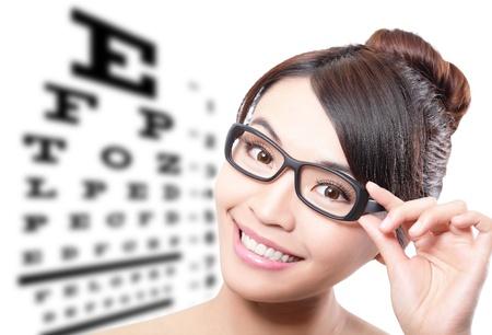 oculista: hermosa mujer con gafas en el fondo de la tabla optom?trica prueba, el concepto de cuidado de los ojos, la belleza asi?tica Foto de archivo