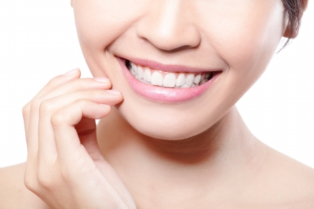 odontologia: Joven y bella mujer dientes de cerca con fingwr. Aislado sobre fondo blanco, modelo de belleza asiática