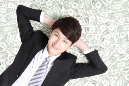 rich people: happy businessman lying on heap of dollars and smiling