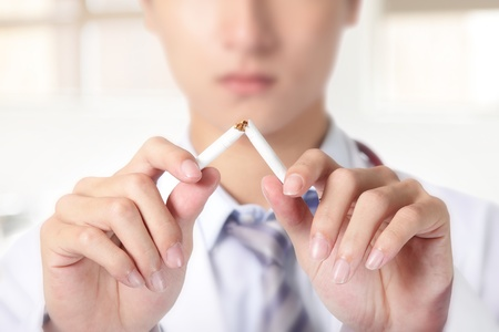 white smoke: Quit smoking, doctor hands breaking the cigarette, close up, asian model Stock Photo