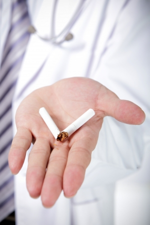 quit smoking: Quit smoking, doctor hands breaking the cigarette, close up, asian model Stock Photo
