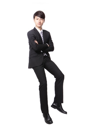 cross arms: Successful business man sitting on something and look to you isolated against white background, asian male model Stock Photo