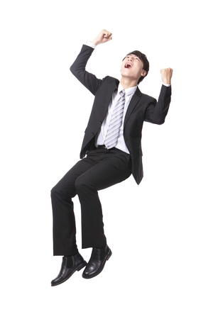 arm chair: Excited handsome business man with arms raised and sitting on something isolated against white background, asian male model Stock Photo