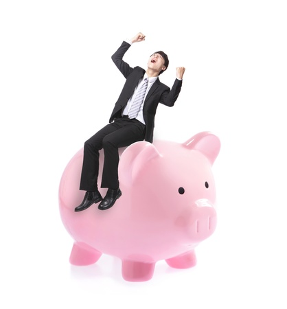 Excited business man with arms raised and sitting on pink piggy bank isolated against white background, asian male model photo
