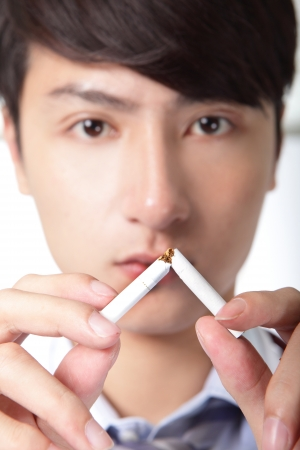 Quit smoking, doctor hands breaking the cigarette, close up, focus on hand, asian model photo