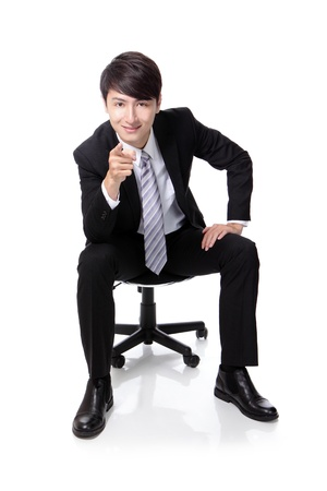 sitting up: Smart businessman smiling and pointing to you while sitting in full length isolated on white background, asian model Stock Photo