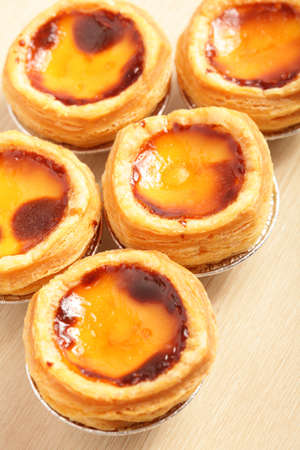 egg tart: delicious portuguese egg tart with copy space on wooden texture table