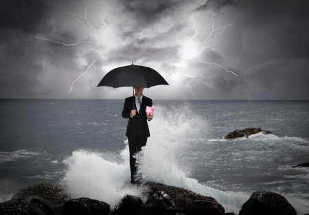 safe water: Business man under an umbrella standing on a rock in the sea with lightning sky, business concept Stock Photo